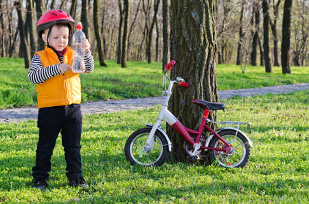 Young little boy rider checking his bottled water as he stops for a drink in a cool shady wooded park with his bicycle propped against a tree nearby