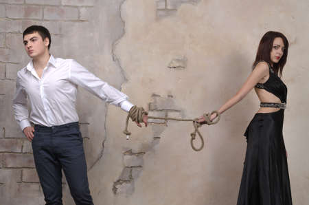 possessive: Image of a male and female model in a studio, their hands tied with a rope