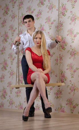 Portrait of woman posing on a swing with her boyfriend photo