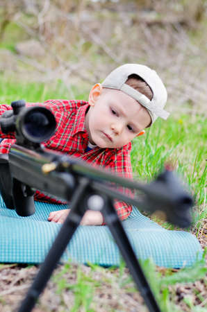 tripod mounted: Portrait of boy on the grass playing with a toy shotgun outdoor Stock Photo
