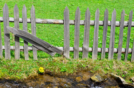 uprights: Line of weathered rustic wooden palisade fencing with two uprights turned sideways to make a partial opening