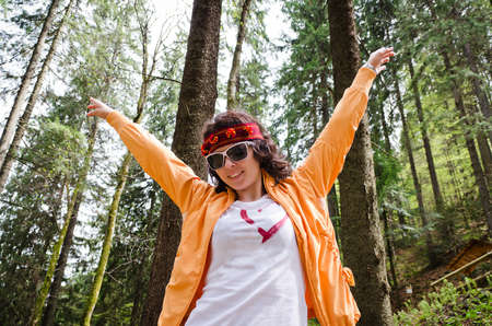Woman rejoicing in her freedom standing on a wooded mountain slope wearing a trendy headband with her arms raised in the air