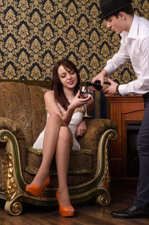 Young man is pouring wine into a glass for the lady
