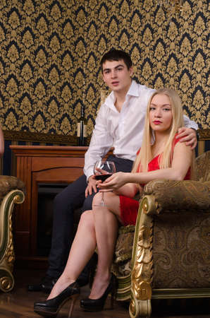 Romantic stylish young couple sitting in an ornately carved armchair in an elegant upmarket interior photo