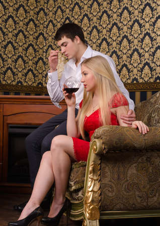 Young couple in vintage room tasting a glass of wine photo