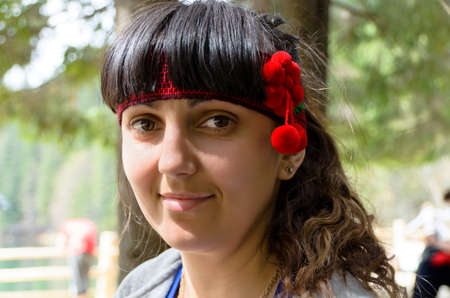 dark haired woman: Attractive dark haired woman in a headband with decorative red pom poms, closeup outdoor portrait