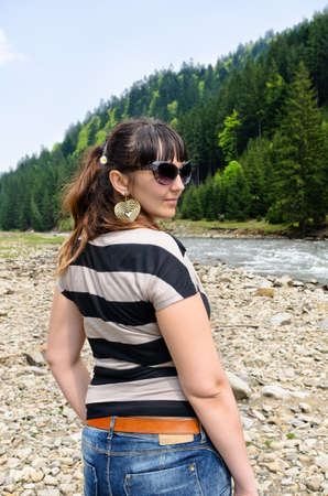 forested: Attractive woman in a mountain valley with forested slopes and a fast flowing stream turning back to look over her shoulder