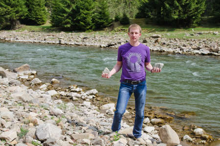 Man standing alongside a fast flowing mountain river holding two rocks from the stony riverbed in his hands photo
