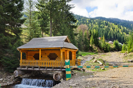 forested: Wooden cabin built over a waterfall supported on two large tree trunks alongside a trail leading through beautiful forested mountain scenery