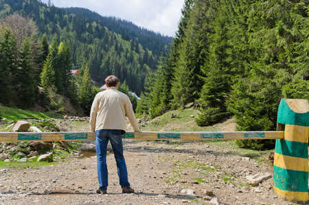 Man standing with his back to the camera admiring a forested valley with steep mountain slopes photo