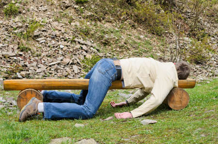 Young man deeply sleeping or drunk, laying outdoors on a wooden park bench  Profile view Stock Photo