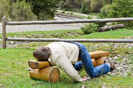 timber bench seat: Young blond man deeply sleeping or drunk, laying outdoors on a wooden park bench  Three-quarters view