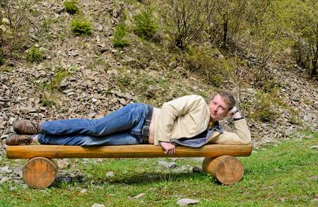 unwinding: Young blond man posing for camera, stretched and laying on his side on a wooden park bench outdoors  Front view