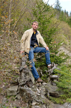 Attractive casual man reclining against a tree stump and rocks on a steep mountain slope in forested terrain photo