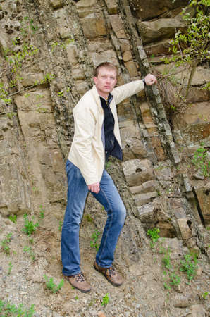Portrait of a man leaning, nonchalantly against rocks on a steep mountain slope photo