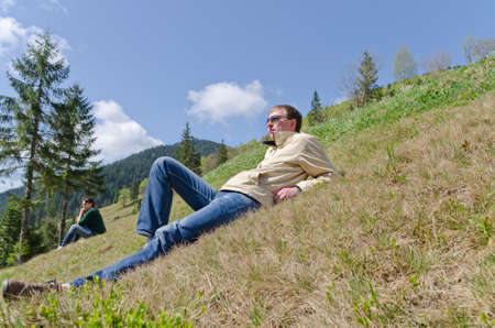 Man and woman enjoying the peace and solitude of nature as they relax on a steep mountain slope overlooking a forested valley Stock Photo - 19904859