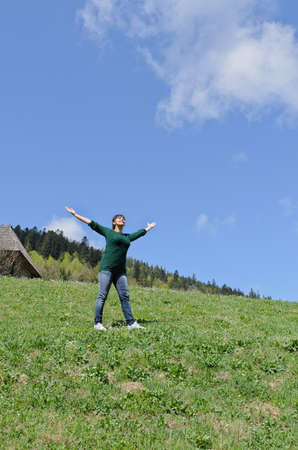 Woman rejoicing in the sunshine standing in the middle of a green mountain field with her arms outspread towards the sun Stock Photo