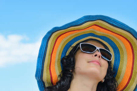 Low angle portrait of a beautiful woman in a wide brimmed colourful striped straw sunhat against a blue sky Standard-Bild