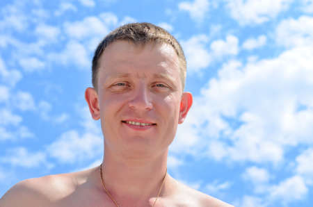 20 24 years old: Portrait of a smiling blond young man against a blue sky with clouds