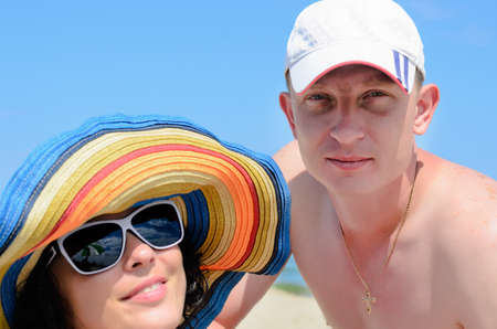 Portrait of a couple sunbathing, both wearing hats photo