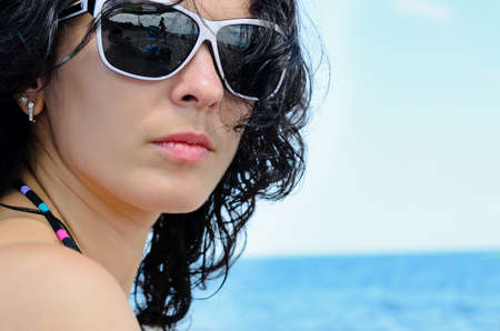 Portrait of a brunette on the beach wearing sunglasses photo
