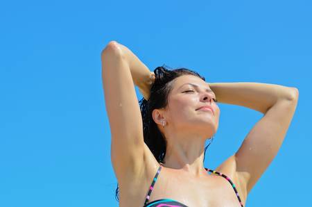 Girl in bikini holding up her hair to enjoying the sun photo