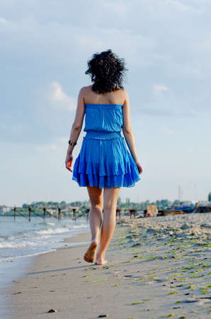Barefoot shapely young woman in a short blue summer dress walking away along a beach with a bridge and town visible in the distance