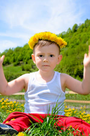 Cheerful young boy raising his hands and sitting on flower field photo