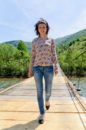 Girl is crossing a river on a wooden bridge photo