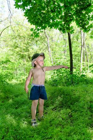 ni�o sin camisa: Ni�o de pie en el bosque mientras que apunta a algo