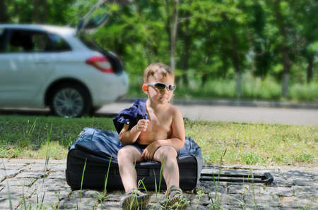 One little boy with glasses sitting on suitcase at the road photo