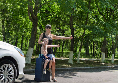 hailing: Mother and child with luggage hailing a taxi on the road