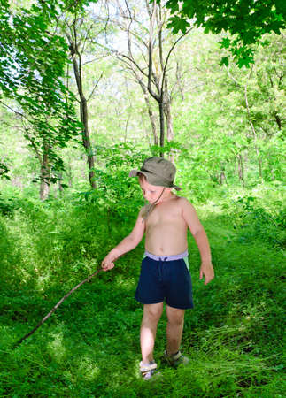 Little toddler boy playing in a forest with stick Stock Photo - 20368029
