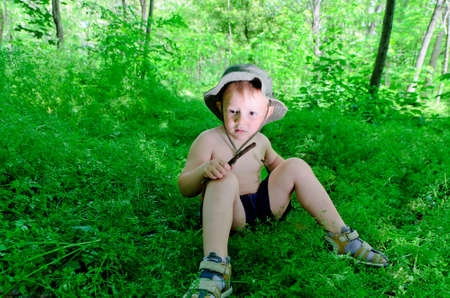 sitting ground: Young boy sitting and playing in the forest Stock Photo