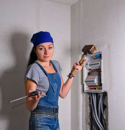 exasperated: Capable young woman wearing a headscarf standing in front of an electrical fuse box shrugging her shoulders while holding a mallet and hammer