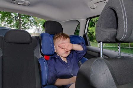 Portrait of young small boy sleeping in a child car-seat