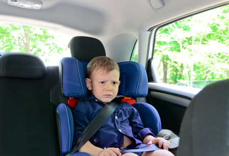 Frowning small boy sitting in child car-seat in a close up shot Archivio Fotografico