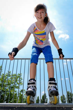 rollerskates: Low angle portrait of an attractive young teenage girl rollerskating standing bent forward balanced on a metal rail wearing blade rollerskates