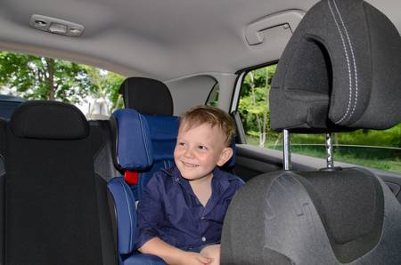 Happy small boy sitting in child car-seat in a close up shot photo
