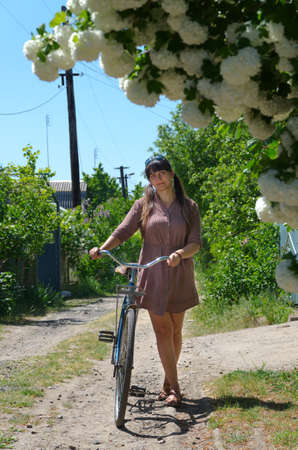 Attractive woman standing holding her a bicycle in spring on a rural lane with overhanging inflorescences of pretty white spring flowers photo