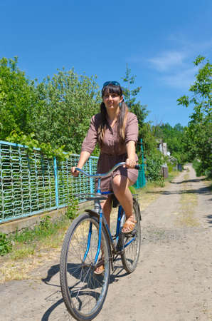 Attractive young woman in a summer dress riding a bicycle down a rural lane in summer sunshine photo