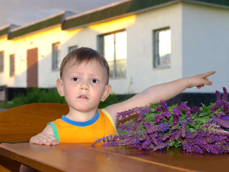 laden: Cute little boy with a concerned expression standing at the edge of a table laden with fresh flowers pointing with his arm
