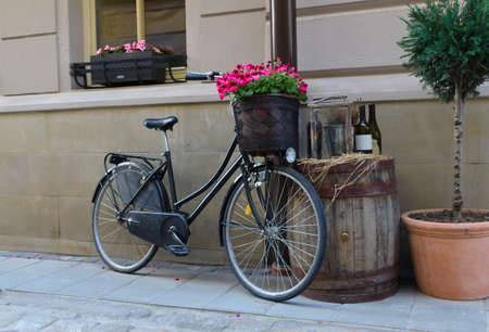 Vintage bicycle with on old barrel full of colourful pink flowers in place of the handlebars used as part of a display in front of a building photo