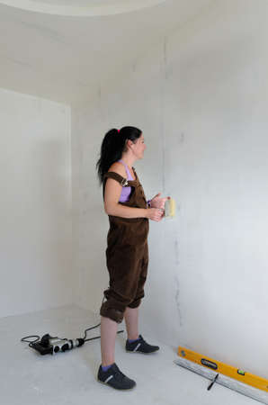 Young woman doing DIY renovating standing in an empty room surrounded by her tools contemplating the wall in front of her photo