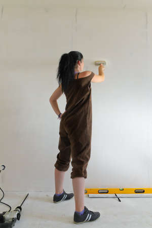 redecorating: Low angle rear view of a competent young woman redecorating her apartment painting the wall Stock Photo