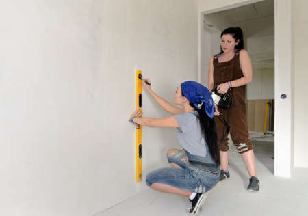Two young women working with a spirit level drawing a straight vertical line on the wall while measuring up to drill a a hole with an electric drill photo