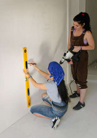 Two women renovating a house using a spirit level to mark a straight line on a wall before drilling a hole with their electric drill photo