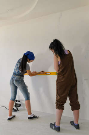 Two girls using a spirit level to mark a straight horizontal line on the wall of a building they are renovating photo