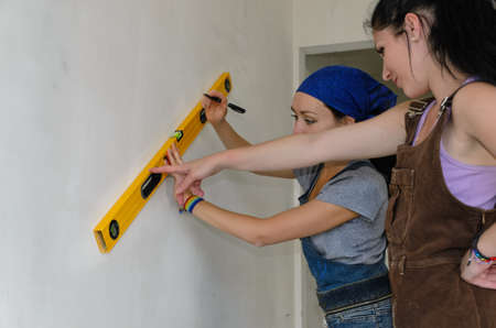 spirit level: Two young female decorators working as a team measuring and marking the wall with a spirit level Stock Photo