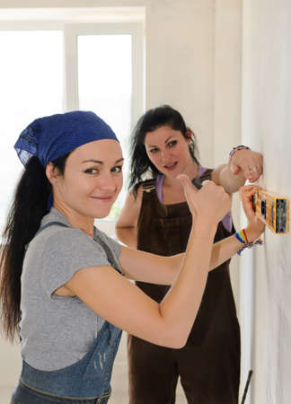 Pretty young woman giving a thumbs up of approval and success while renovating an apartment with a friend who is helping her align a spirit level on the wall photo